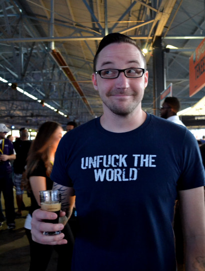 Crafty fellow in a clever shirt enjoying his brew and smirking.